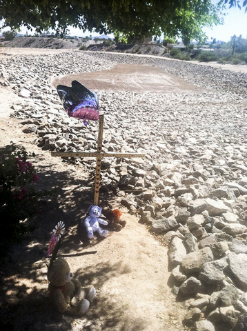 Balloons and stuffed toys are near the lot at Chaparral and Country Club drives in Bullhead City, Arizona, where the body believed to be 8-year-old Isabella Grogan-Cannella was found Wednesday. (A ...
