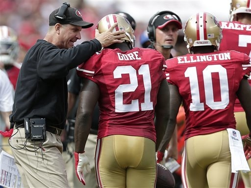 San Francisco 49ers running back Frank Gore (21) is congratulated by head coach Jim Harbaugh after scoring on a 55-yard touchdown reception against the Philadelphia Eagles during the second quarte ...