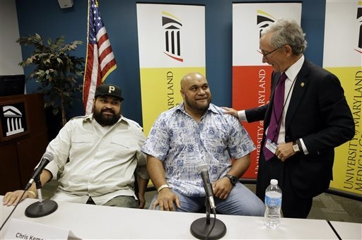 Chris Kemoeatu, left, and his brother Ma'ake chat with Dr.  Matthew Weir after a news conference at the University of Maryland Medical Center, Wednesday, Sept. 17, 2014, in Baltimore. Chris Kemoea ...