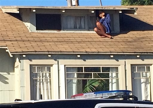 In this Wednesday, Sept. 24, 2014 photo, Laura Rivera, who fled her house through an attic window to escape an intruder, waits for help after an early-morning break-in at her house in the Venice n ...