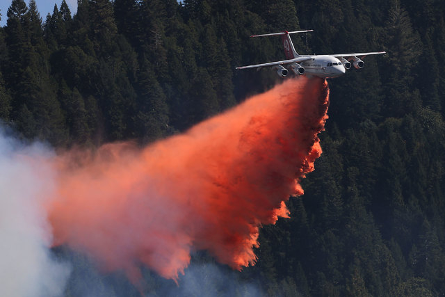 A jet aerial tanker drops its load of fire retardant on a fire near Pollack Pines, California., Monday, Sept. 15, 2014. The fire, which started Sunday, has consumed more than 3,000 acres and force ...