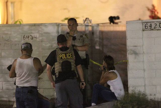 Las Vegas police interview people in front of apartments in the 6400 block of Casada Way, near Charleston and Rainbow boulevards in Las Vegas where a robbery and car jacking occurred Wednesday. Po ...