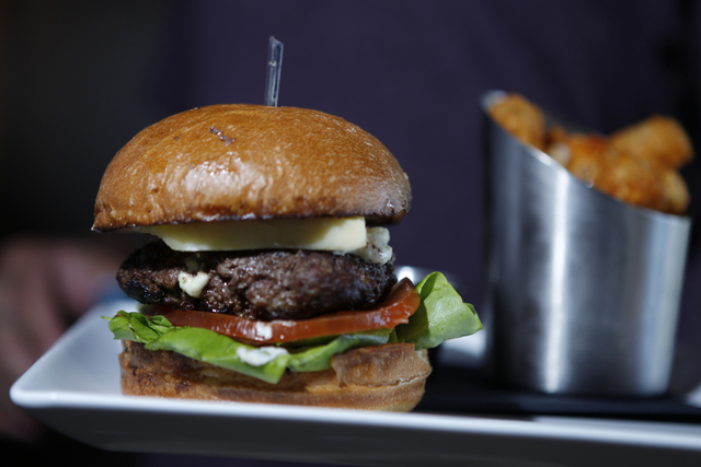 A butter burger is seen served with boursin cheese, cheddar, lettuce, and tomato with a side of tater tots during dinner service at Carson Kitchen restaurant, 124 S. Sixth St. in Las Vegas, is see ...