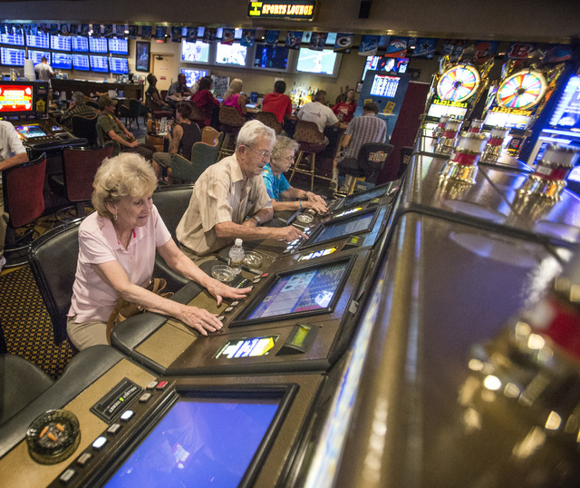 Marilyn Morrell,left, Jim Horbelt and his wife Betty play video poker in the Railroad Pass hotel-casino in Henderson, Nevada on Friday, Sept. 5, 2014.  MGM International is selling Railroad Pass t ...
