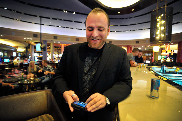 Club promoter Chris Hornak checks the status of his customers as he waits for their arrival at the Palms hotel-casino on Friday, Aug. 29, 2014. (David Becker/Las Vegas Review-Journal)