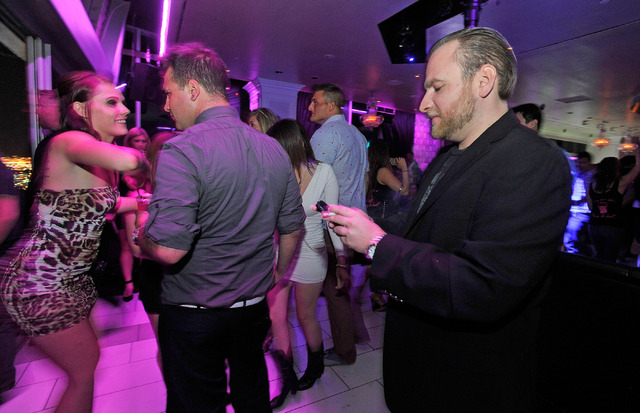 Club promoter Chris Hornak, right, keeps in touch with his customers as he spends a few minutes inside the Ghostbar checking on others at the Palms hotel-casino on Friday, Aug. 29, 2014. (David Be ...