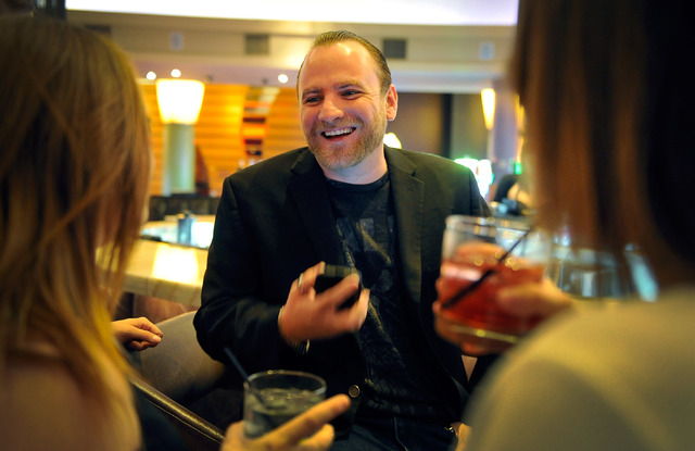 Club promoter Chris Hornak, center, reviews the night's schedule as he shares a drink with his employees, before the arrival of a group of customers at the Palms hotel-casino on Friday, Aug. 29, 2 ...