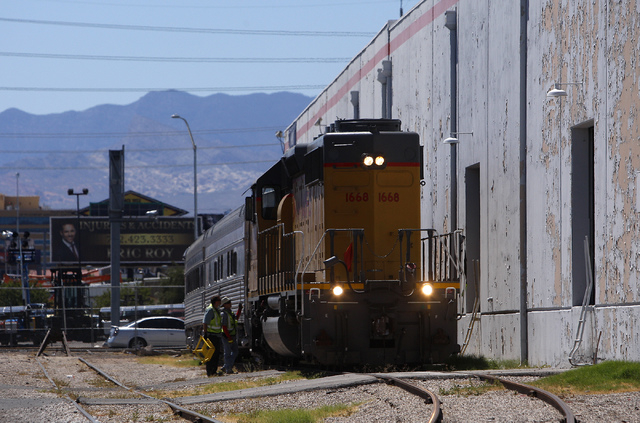 Union Pacific workers prepare a pair of Club X Train cars to be moved from the Las Vegas Review-Journal's parking lot near the intersection of MLK Blvd. and Bonanza Rd. in Las Vegas on Thursday, J ...