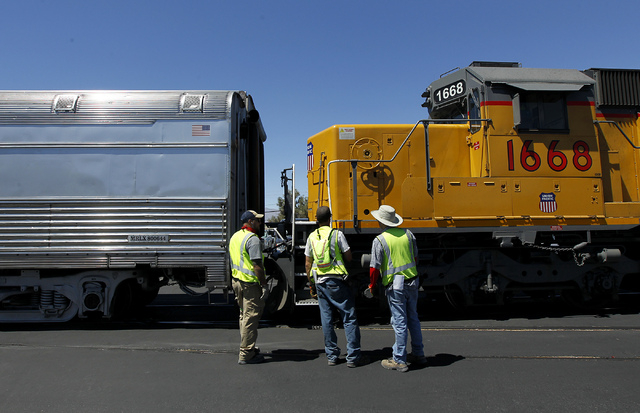 Union Pacific workers prepare a pair of Club X Train cars to be removed from the Las Vegas Review-Journal's parking lot near the intersection of MLK Blvd. and Bonanza Rd. in Las Vegas on Thursday, ...