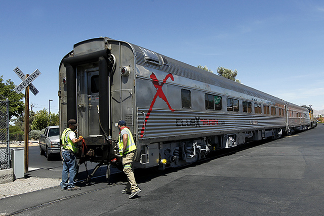 Union Pacific workers prepare a pair of Club X Train cars to be moved from the Las Vegas Review-Journal's parking lot on Thursday, July 24, 2014. (Jason Bean/Las Vegas Review-Journal)