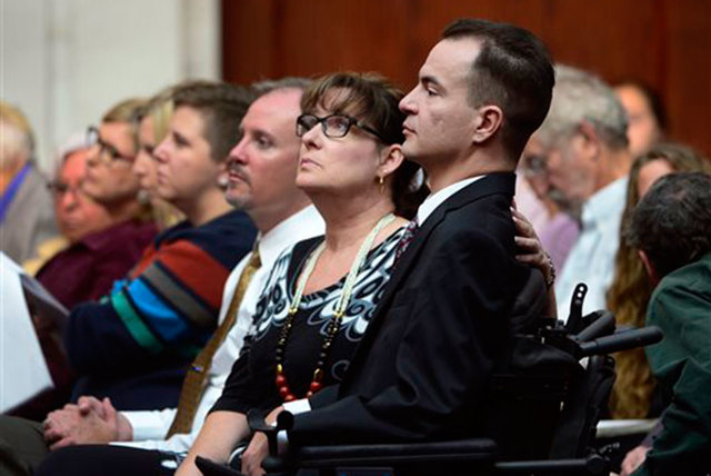 Brandon Coats, a quadriplegic medical marijuana patient who was fired by the Dish Network after failing a drug test more than four years ago, right, waits for the proceedings to begin with his mot ...