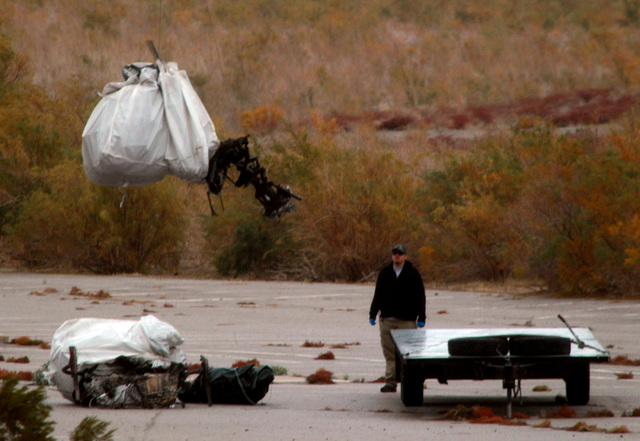 JEFF SCHEID/LAS VEGAS REVIEW-JOURNAL A man watches while a helicopter lowers a charred piece of wreckage of a sightseeing helicopter near Boulder Harbor at Lake Mead on Monday, Dec. 12, 2011. The  ...