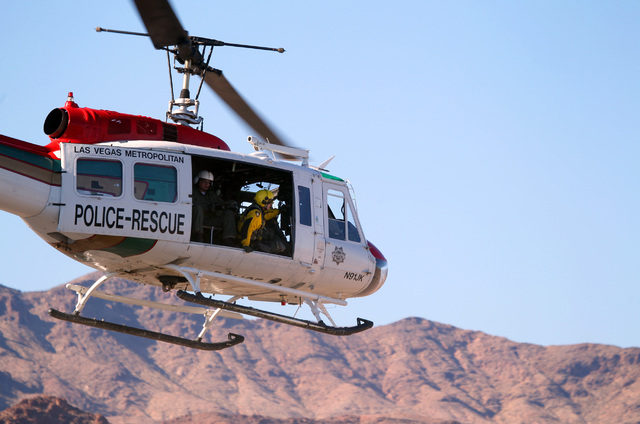 A Las Vegas police search and rescue helicopter lifts off at the Model Aircraft area  at Lake Mead National Recreation Area while heading to helicopter crash site in the mountains in the backgroun ...