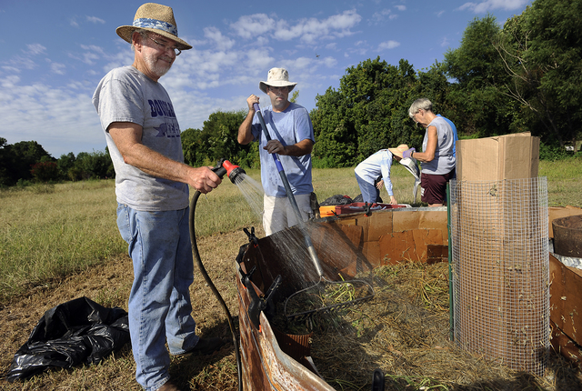 Nacogdoches County Master Gardener interns Kent Ferguson, left, and Paul Sims water and level plant waste for the base material in a keyhole garden on Thursday, Aug. 28, 2014, in Nacogdoches, Texa ...