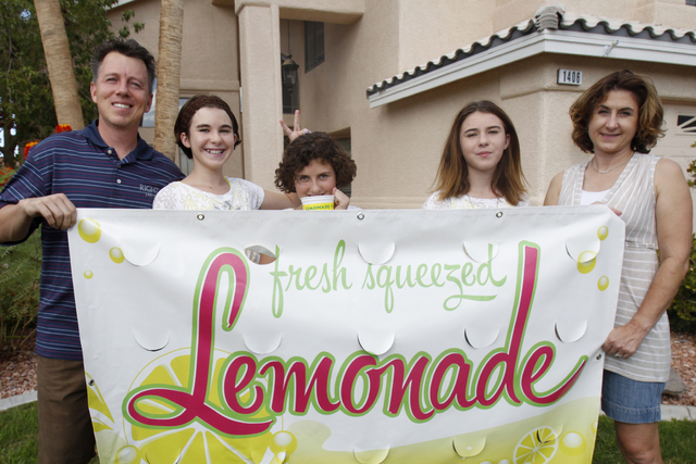 Rock Rocheleau, from left, with his daughters Jordan, 12, Jessica, 10, and Jenna, 12, and his wife Stacy, pose for a portrait with their lemonade sign at their home in Henderson Saturday, Sept. 6, ...