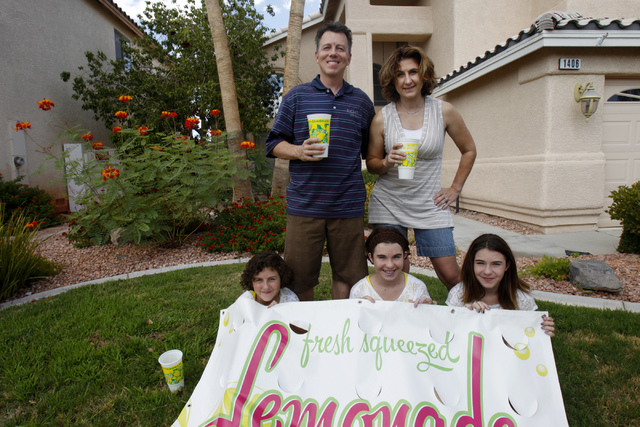 Rock Rocheleau, clockwise from back left, his wife Stacy, and daughters Jenna, 12, Jordan 12, and Stacy, 10, pose for a portrait with their lemonade sign at their home in Henderson Saturday, Sept. ...