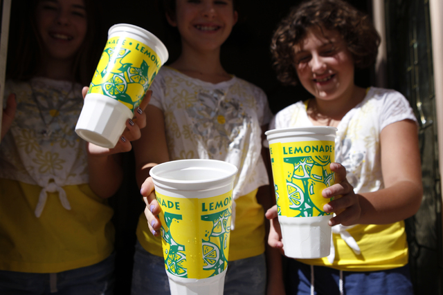 Sisters Jenna Rocheleau, from left, 12, her twin Jordan 12, and Stacy, 10, pose for a portrait holding the lemonade cups they use to sell their lemonade at their home in Henderson Saturday, Sept.  ...