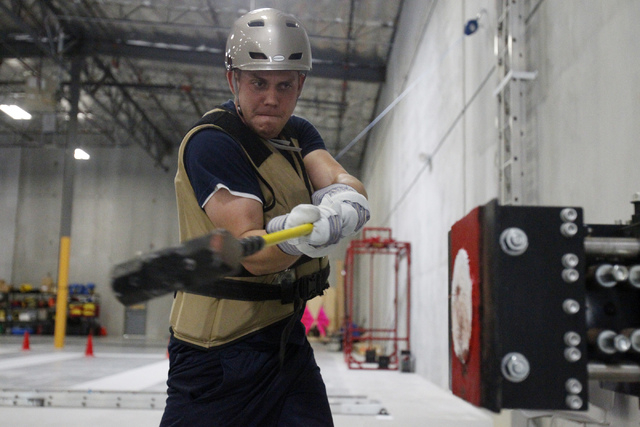 Shane Gammon, Candidate Physical Ability Test proctor, swings a sledge hammer in the forcible entry event during a media CPAT course demonstration at their facility in Las Vegas Thursday, Sept. 11 ...