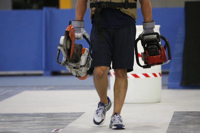 Shane Gammon, Candidate Physical Ability Test proctor, carries a couple of chainsaws in the equipment carry event during a media CPAT course demonstration at their facility in Las Vegas Thursday,  ...