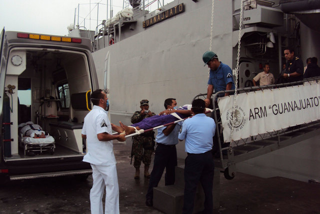 Mexican marines carry a dehydrated Cuban migrant on a stretcher after they were rescued off the coast of Yucatan on Monday, Sept. 1, 2014. More than two dozen Cuban rafters were rescued off the co ...