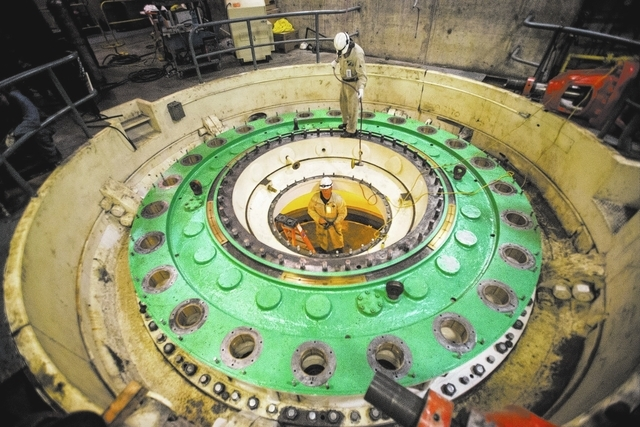 Kevin Zito, top, hands  David Polan a grinder while then prep for a turbine installation at Hoover Dam on Thursday, March 20, 2014.Almost two-fifths of the workforce at the federal facility is exp ...