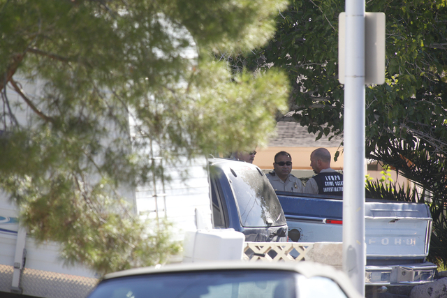 Relatives look on as Las Vegas police investigate a shooting at a home on the 5100 block of Del Rey Avenue, near near Charleston and Decatur boulevards, in Las Vegas on Wednesday, Sept. 3, 2014. T ...