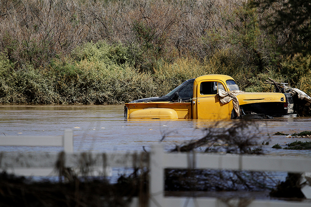 A car stands in flood waters in a neighborhood near the Muddy river in Overton on Tuesday, Sept. 9, 2014. High flood waters filled homes and caused damage in the neighborhood. (Justin Yurkanin/Las ...