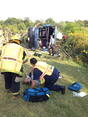 Passengers from a tour bus are treated for injuries after the bus overturned Sunday, Sept. 21, 2014, on a highway near Bear, Del. Two people died and several others were injured in the crash, offi ...