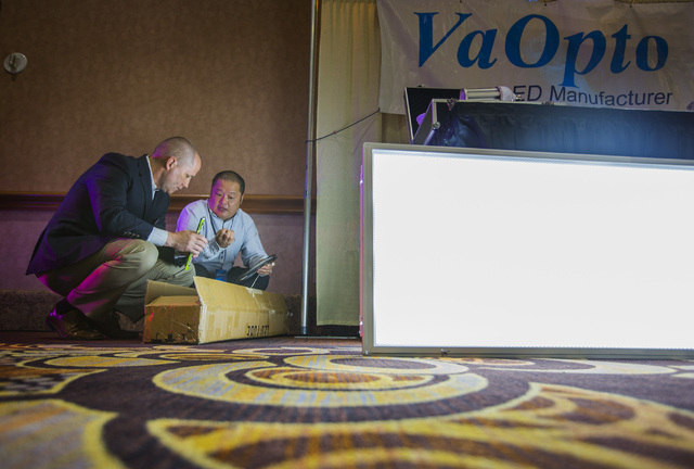 Charles Li, right, president of VaOpto, talks to Bob Carlson, assistant director of facilities for Mandalay Bay, about LED lighting during National Clean Energy Summit 7.0: Partnership & Progress  ...