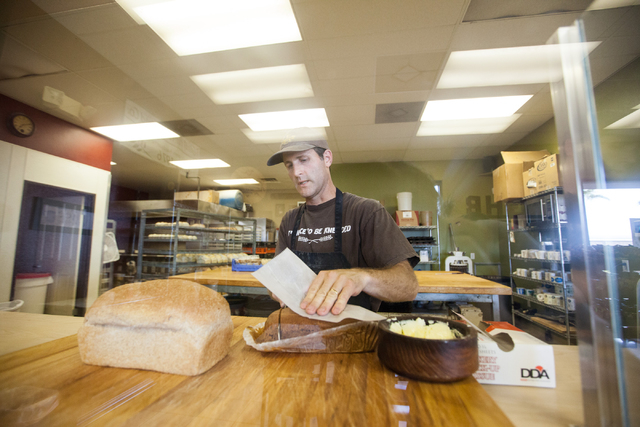 Marcus Stewart cuts a slice of bread at his bakery, Great Harvest Bread, 4800 E. Bonanza Road. (Chase Stevens/View)