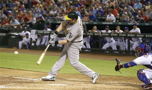 Oakland Athletics designated hitter Adam Dunn (10) hits a two run RBI double in front of Texas Rangers catcher Robinson Chirinos (61) during the third inning of a baseball game in Arlington, Texas ...