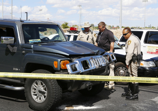 Las Vegas police officers and a crash investigator survey the damage to an SUV on Friday, Sept. 26, 2014, in the 4900 block of Tropicana Avenue, near Decatur Boulevard. A man was struck by a car,  ...