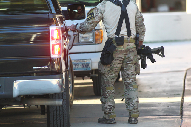 An FBI agent holds an assault rifle as an investigation goes on while serving a federal search warrant at a home at 4311 E. Oquendo Road in Las Vegas on Monday, Sept. 29, 2014. The FBI did not giv ...