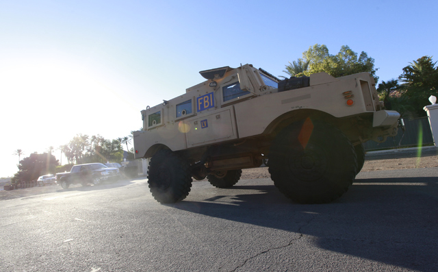 An FBI vehicle leaves the scene as agents investigate while serving a federal search warrant at a home at 4311 E. Oquendo Road in Las Vegas on Monday, Sept. 29, 2014. The FBI did not give any othe ...