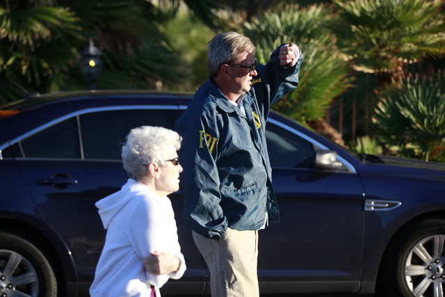 Neighborhood resident Myrna Cameron questions an unidentified FBI official as the FBI investigates while serving a federal search warrant at a home at 4311 E. Oquendo Road in Las Vegas on Monday,  ...