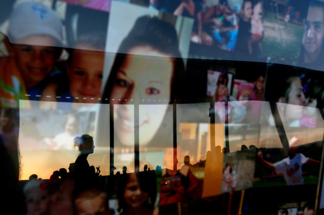 Mourners are reflected in a framed collage of images featuring Sarah Spirit and her children during a candlelight vigil at Bell Elementary for the victims of Thursday's shootings on Sunday, Sept.  ...