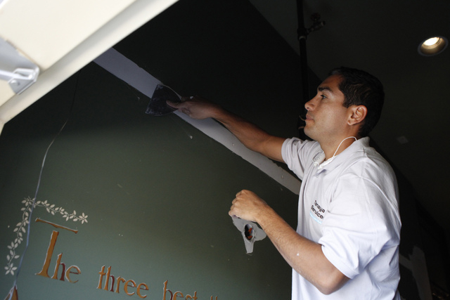 Painter Mario Zavala resurfaces a wall for painting at Sean Patrick's pub and grill, formerly Molly Malone's Irish Pub, 11930 Southern Highlands Parkway in Las Vegas Thursday, Sept. 4, 2014. The l ...