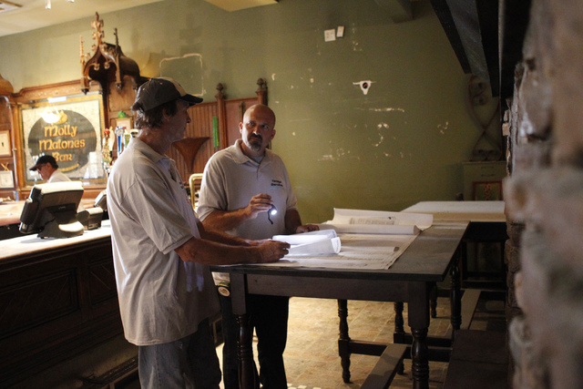 Tenaya Services general contractor employees, carpenter Scott Rieger, left, and project manager Scott Kiser, look at project information at Sean Patrick's pub and grill, formerly Molly Malone's Ir ...