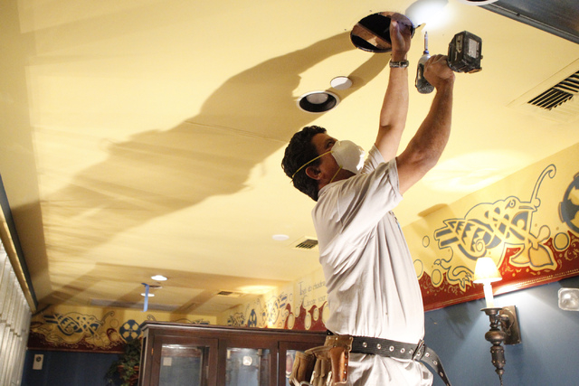 Jorge Meza, team supervisor with Tenaya Services, covers an opening on the ceiling at Sean Patrick's pub and grill, formerly Molly Malone's Irish Pub, 11930 Southern Highlands Parkway in Las Vegas ...