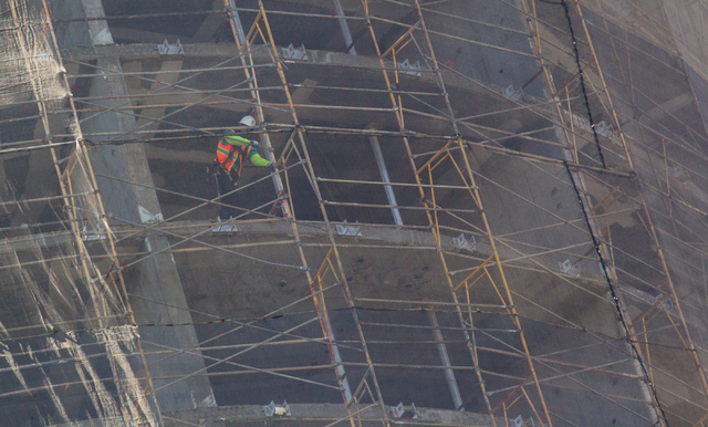 Construction crews, including a man on upper left, work on demolishing the unfinished Harmon Hotel at CityCenter in Las Vegas on Monday, Sept. 22, 2014. The building is being taken down because it ...