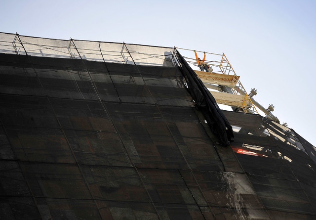 A worker installs scaffolding along the top edge of the Harmon Hotel as the demolition of the unfinished tower continues Monday, Sept. 22, 2014, in Las Vegas. The planned 47-story tower, part of M ...