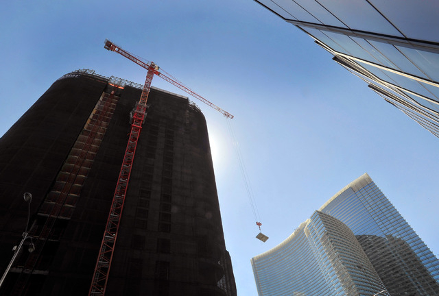 A tower crane lowers a concrete slab as the demolition continues of the unfinished Harmon Hotel tower on Monday, Sept. 22, 2014, in Las Vegas. The planned 47-story tower, part of MGM Resort Intern ...