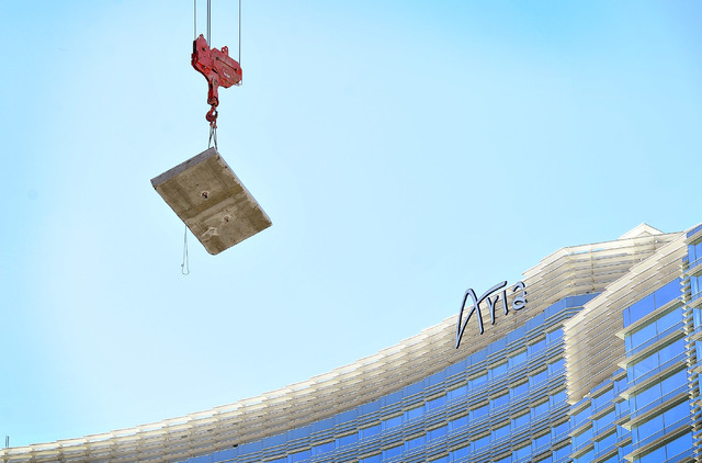 A tower crane lowers a concrete slab by the Aria hotel-casino as the demolition continues of the unfinished Harmon Hotel tower on Monday, Sept. 22, 2014, in Las Vegas. The planned 47-story tower,  ...