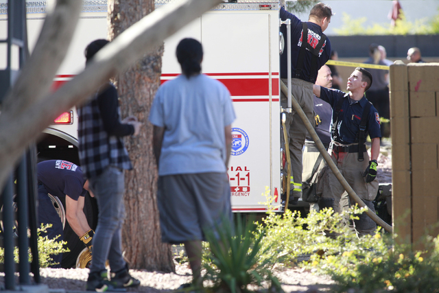 Firefighters clean up as residents look on after responding to a fire that left one man dead in an apartment complex on 2825 Bluegrass Lane in Henderson  on Tuesday, Sept. 30, 2014. (Chase Stevens ...