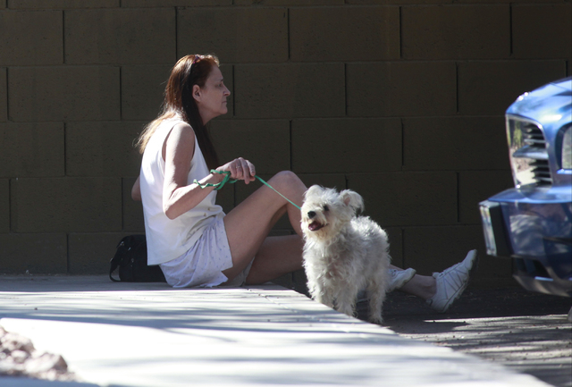 Teri English, who lives in the building where a fire left one man dead, sits with her miniature schnauzer Twitch as firefighters investigate the scene at an apartment complex on 2825 Bluegrass Lan ...
