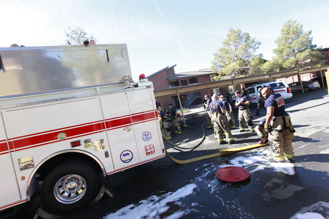 Firefighters clean up after responding to a fire that left one man dead in an apartment complex on 2825 Bluegrass Lane in Henderson  on Tuesday, Sept. 30, 2014. (Chase Stevens/Las Vegas Review-Jou ...