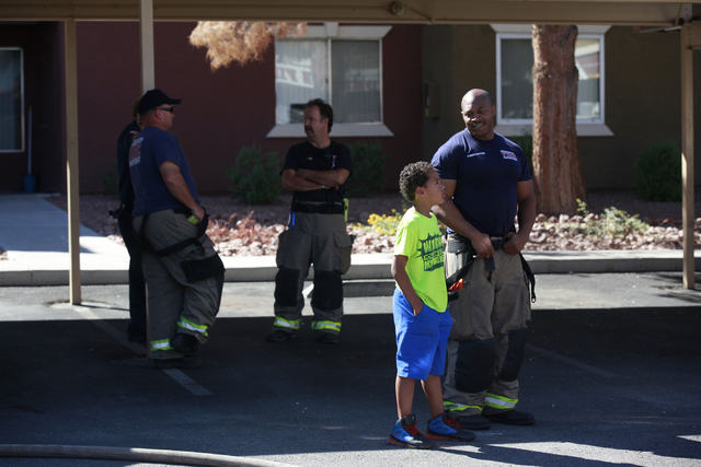 Firefighter Eric Mathews, right, talks with resident Jason Reddick, 8, after firefighters responded to a fire that left one man dead in an apartment complex on 2825 Bluegrass Lane in Henderson  on ...