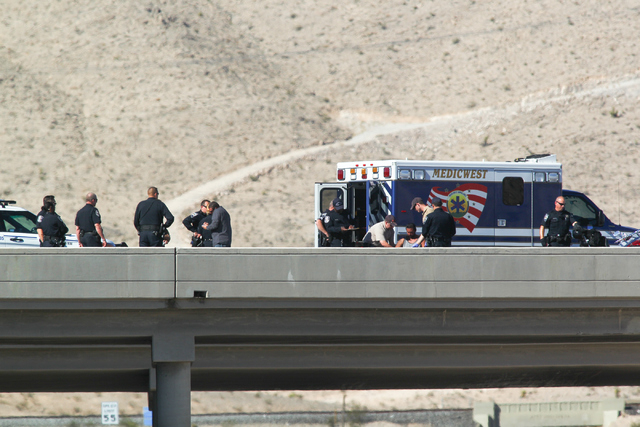 The man who threatened to harm himself, fourth from right, is seen on a gurney with Nevada Highway Patrol and North Las Vegas police officers, along with negotiators, on the I-15 at the Las Vegas  ...