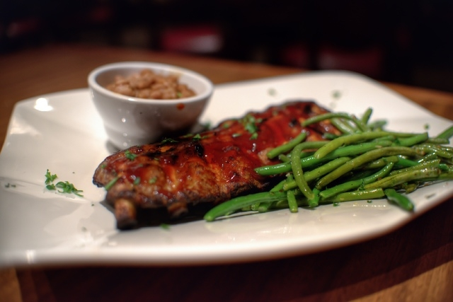 The half rack of barbecue pork ribs at Cafe V's comes with beans and a choice of baked or mashed potatoes, fries or rice. (Fernando Lopez/Special to View)