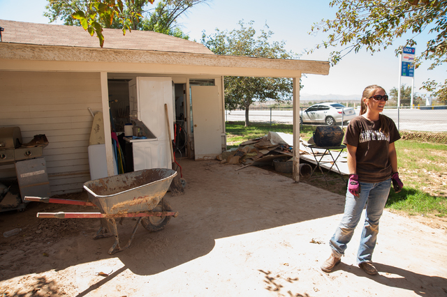 Resident Heidi Greig, of Moapa, Nev., cleans up damage to her home just off exit 91 on Interstate 15 on Saturday Sept. 13, 2014. (Martin S. Fuentes/Las Vegas Review-Journal)